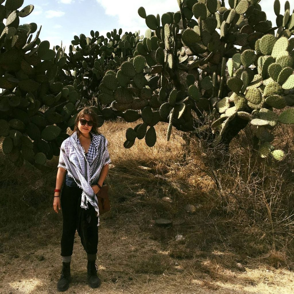 Sabina stands in a field in front of several big cacti plants. They're wearing black pants, sunglasses, and a white and black checkered scarf.